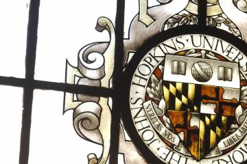 Johns Hopkins University seal depicted in a stained-glass window in Gilman Hall